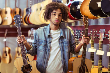dudando: Handsome Afro-American man holding two guitars in both hands and hesitating which to choose; standing in a musical shop
