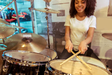 Beautiful Afro-American girl in white t-shirt smiling while playing drums in a musical shop