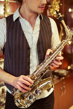 hombres jovenes: Handsome stylish man in classical vest holding a saxophone while standing in a musical shop, cropped