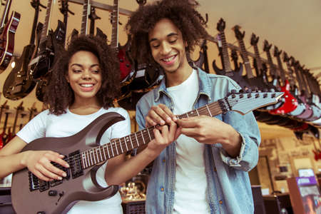 chords: Beautiful young Afro-American couple standing in a musical shop. Girl playing an electric guitar and smiling while man helping her with chords