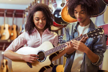 chords: Beautiful young Afro-American couple standing in a musical shop. Girl playing a guitar and smiling while man helping her with chords