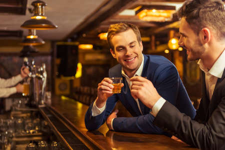 Two young businessmen in suits are smiling and clanging glasses of alcoholic beverage together while sitting at bar counter in pub