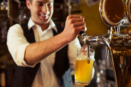 Handsome bartender is smiling and filling a glass with beer while standing at bar counter in pub, close-up
