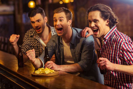 Three young men in casual clothes are cheering for football and holding bottles of beer while sitting at bar counter in pub