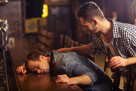 near beer: Young man in casual clothes is sleeping near the bottle of beer on a bar counter in pub, another man is waking him up