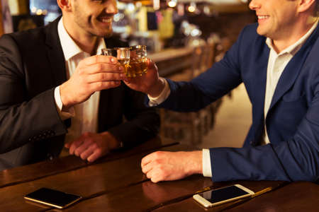 Two young businessmen are smiling and clanging glasses of  alcoholic beverage together while sitting in pub