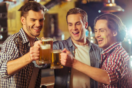 near beer: Three young men in casual clothes are smiling and clanging glasses of beer together while standing near bar counter in pub Stock Photo
