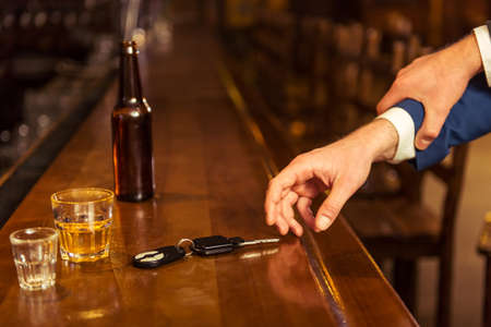 reach customers: Young drunk businessman is holding a bottle of beer and reaching car keys on bar counter in pub, another man is stopping him, close-up