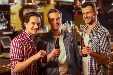 near beer: Three young men in casual clothes are smiling, looking at camera and holding bottles of beer while standing near bar counter in pub Stock Photo