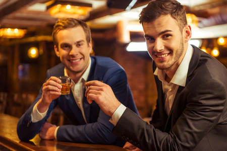 Two young businessmen are smiling, looking at camera and clanging glasses of alcoholic beverage together while sitting at bar counter in pub Stock Photo