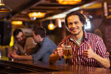 Young dark haired man in casual clothes is smiling, looking at camera, showing OK sign and drinking beer while sitting at bar counter in pub