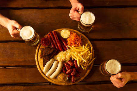 near beer: Top view of hands holding glasses of beer, a big wooden tray with delicious snacks near, on wooden background