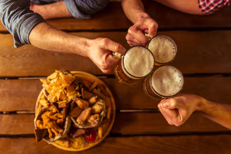 big top: Top view of hands clanging glasses of beer together, near big wooden tray with delicious snacks, on wooden background Stock Photo