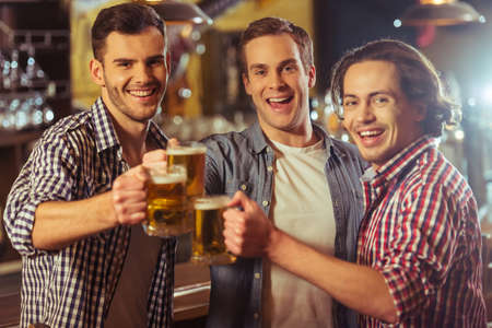 near beer: Three young men in casual clothes are smiling, looking at camera and clanging glasses of beer together while standing near bar counter in pub