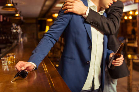 reach customers: Young drunk businessman is holding a bottle of beer and reaching car keys on bar counter in pub, another man is stopping him