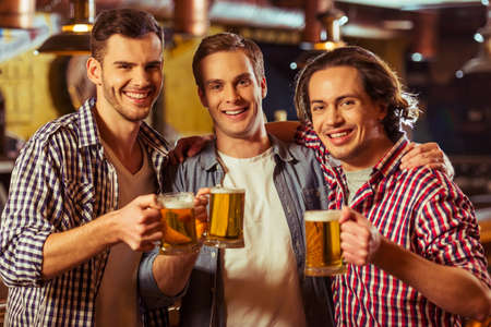 near beer: Three young men in casual clothes are smiling, looking at camera and holding glasses of beer while standing near bar counter in pub Stock Photo