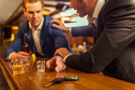 reach customers: Young drunk businessman is holding a bottle of beer and reaching car keys while sitting at bar counter in pub, another man is stopping him