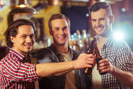 near beer: Three young men in casual clothes are smiling, looking at camera and clanging bottles of beer together while standing near bar counter in pub Stock Photo