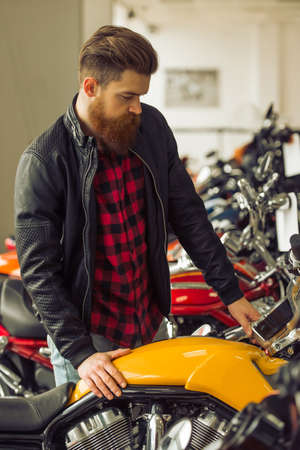 Handsome young bearded man in black leather jacket is examining motorbikes in a motorbike salon