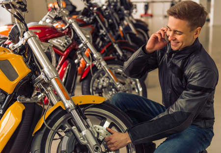cool gadget: Attractive young blond man in black leather jacket is talking on the mobile phone and smiling while examining a motorbike