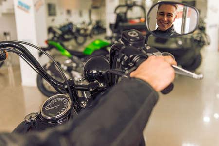 reflexion: Atractiva joven rubia en chaqueta de cuero negro está mirando su reflejo en el espejo de moto y sonriente