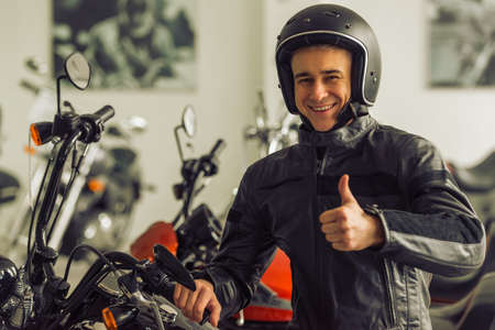 new look: Attractive young blond man in black leather jacket and helmet is looking at camera, showing Ok sign and smiling while sitting on a motorbike