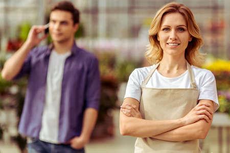 mandil: Joven y bella mujer en el delantal está mirando la cámara y sonriendo mientras está de pie en el invernadero, el hombre en el fondo
