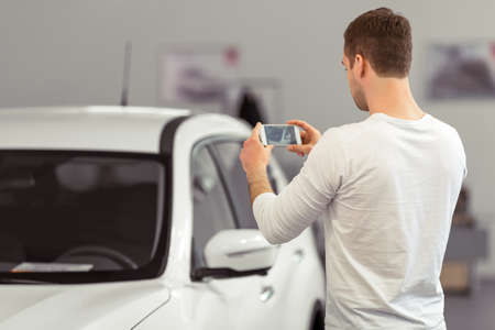 car salesperson: Back view of handsome young man making a photo of car using smart phone while standing in a motor show