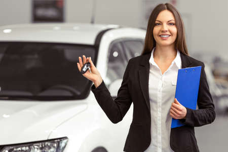 automobile dealership: Beautiful young woman in classic suit is smiling, looking at camera and holding car keys while presenting car in a motor show Stock Photo