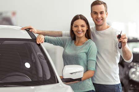 Hermosa joven pareja está sonriendo y mirando a la cámara mientras se inclina sobre su nuevo coche en un salón del automóvil. El hombre está sosteniendo las llaves del coche