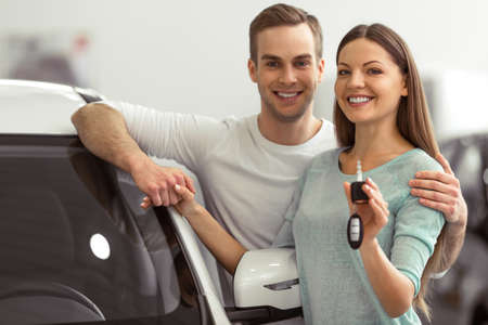 Beautiful young couple is smiling and looking at camera while leaning on their new car in a motor show. Woman is holding car keys Stock Photo