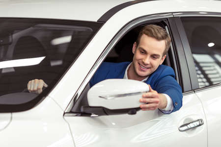 new classic: Handsome young businessman in classic blue suit is smiling and looking in the side mirror while sitting in car in a motor show