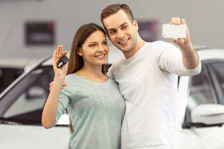 Beautiful young couple is smiling and making a selfie using a smart phone while buying a car in a motor show. Woman is holding keys