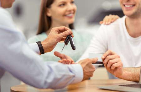 El par joven está sonriendo mientras que la compra de un coche, trabajador de mediana edad de un salón del automóvil está dando claves, primer plano
