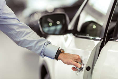 Middle aged businessman in classic shirt is opening a car in a motor show, close-up
