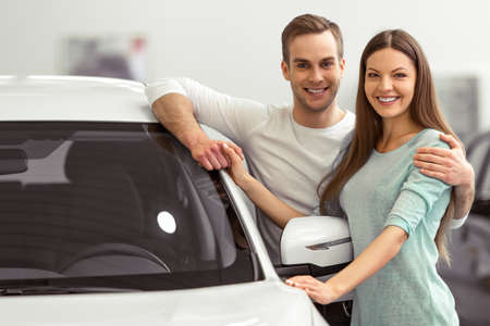 new motor vehicles: Beautiful young couple in casual clothes is smiling and looking at camera while leaning on their new car in a motor show