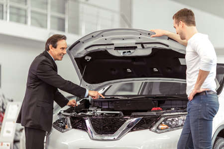 salesman: Handsome middle aged salesman is showing a car engine to handsome young customer in a motor show