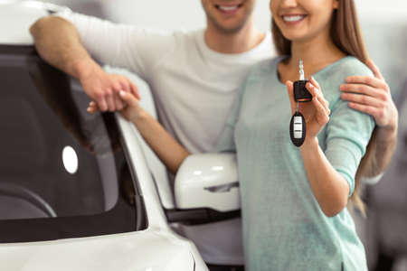 Hermosa joven pareja está sonriendo y mirando a la cámara mientras se inclina sobre su nuevo coche en un salón del automóvil. La mujer está sosteniendo las llaves del coche, primer plano Foto de archivo