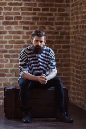 striped vest: Stylish young bearded man in striped vest is looking at camera, sitting against brick wall