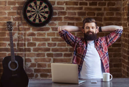 Handsome young bearded man in casual clothes is resting and smiling after working with a laptop