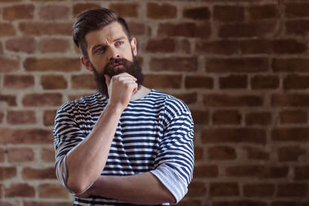striped vest: Thoughtful young bearded man in striped vest is looking away, standing against brick wall Stock Photo