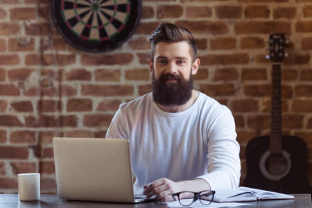 Handsome young bearded businessman in white sweatshirt is using a laptop, looking at camera and smiling while working