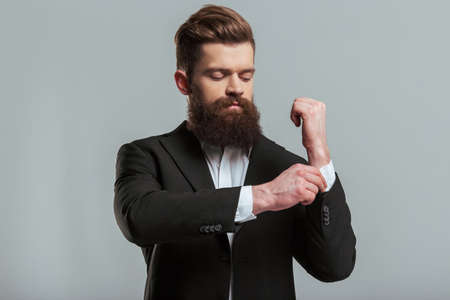 cufflink: Handsome young bearded businessman in classic suit is adjusting his cufflink, on a gray background