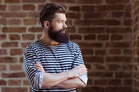 striped vest: Stylish young bearded man in striped vest is looking away, standing against brick wall Stock Photo