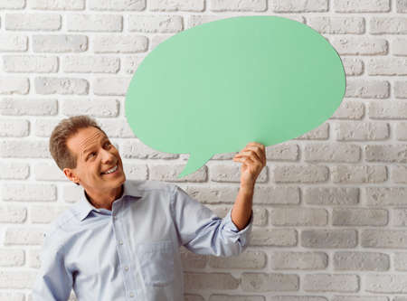 text bubble: Handsome middle aged man is holding a green speech bubble, looking at it and smiling while standing against white brick wall Stock Photo