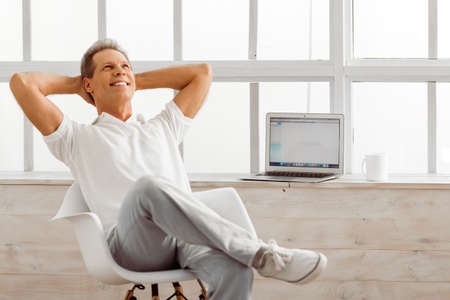 mature business man: Handsome middle aged man in casual clothes is resting, sitting on a chair near the window at home, laptop in the background