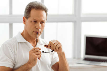 Thoughtful middle aged man is holding eyeglasses and thinking while sitting near the window at home, laptop in the background