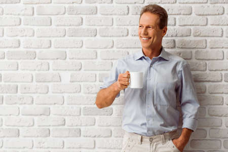 Apuesto hombre de mediana edad está sosteniendo una taza, sonriendo y mirando a otro lado mientras está de pie contra la pared de ladrillo blanco