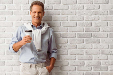 adult wall: Handsome middle aged man is holding a cup, looking at camera and smiling while standing against white brick wall Stock Photo