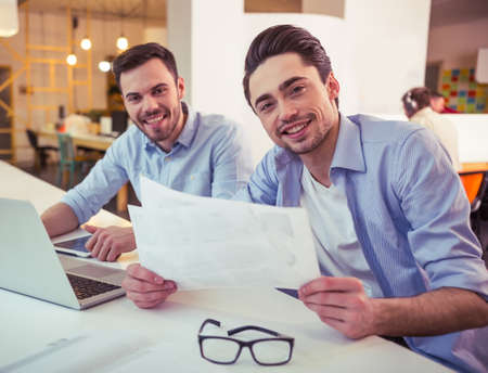 freelancers: Handsome young freelancers are using a laptop, talking and smiling while working at the modern office